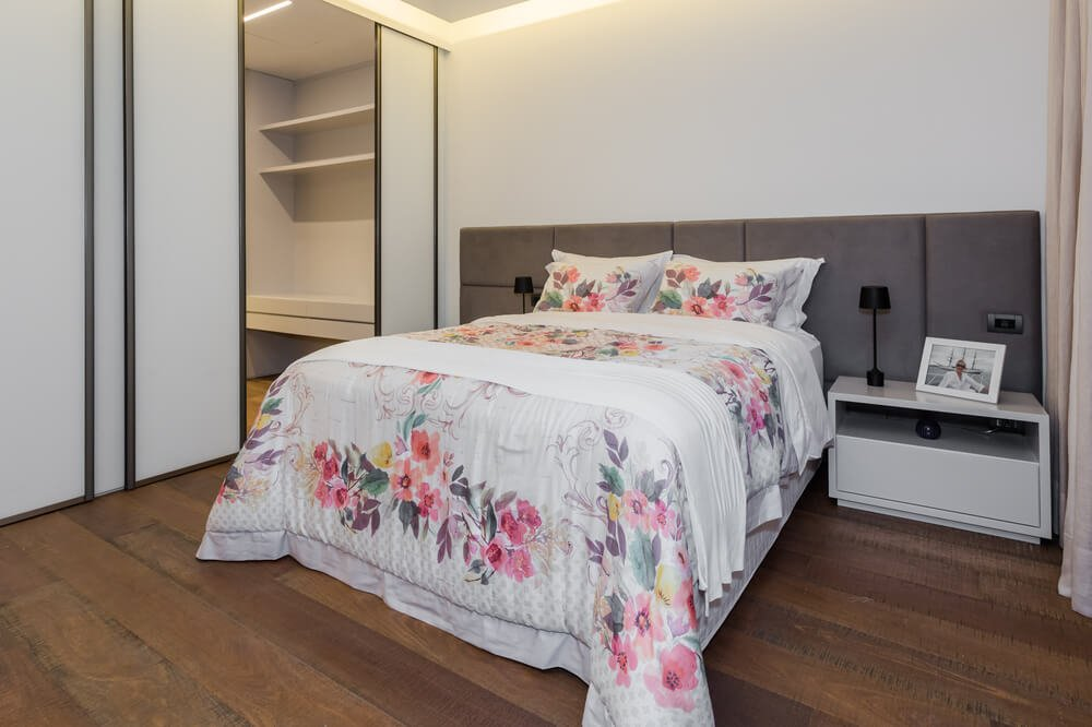 This simple bedroom has a floral bed complemented by the built-in cushioned headboard and flanking white bedside drawers bearing small black table lamps.