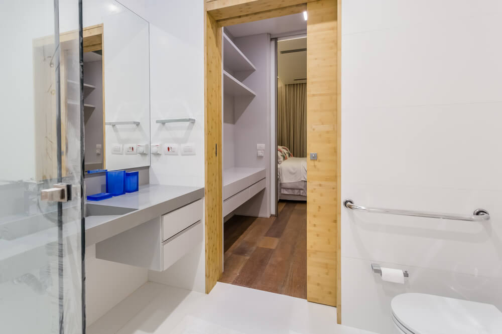 This bathroom has a floating sink across from the toilet and beside the shower area.