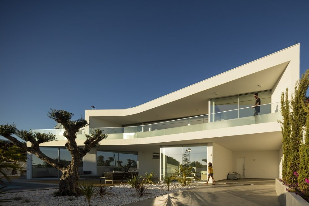 Tis large adobe house has beige walls complemented by the abundant glass walls and windows.