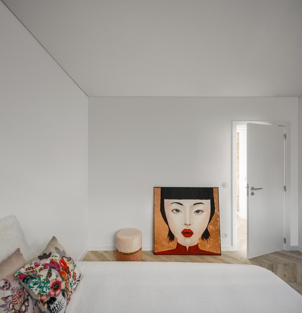 This is the bedroom that has white walls, a white bed and herringbone flooring that is adorned by the artworks on the side.