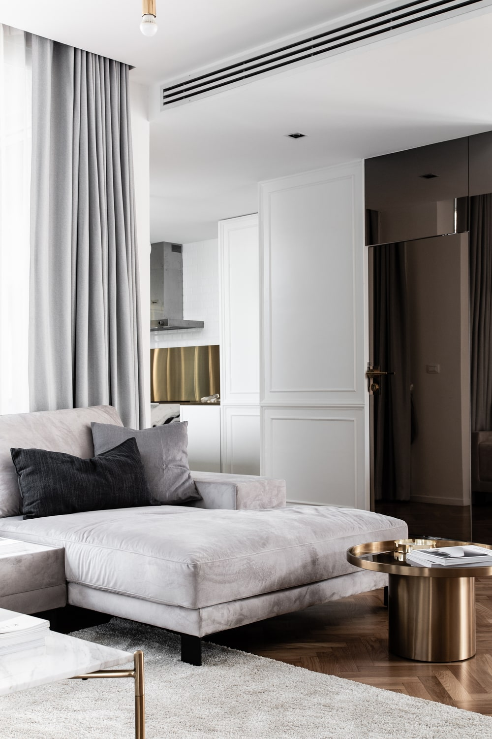 This is a large day bed sofa on the far end of the family room that is also paired with a small metallic round end table.