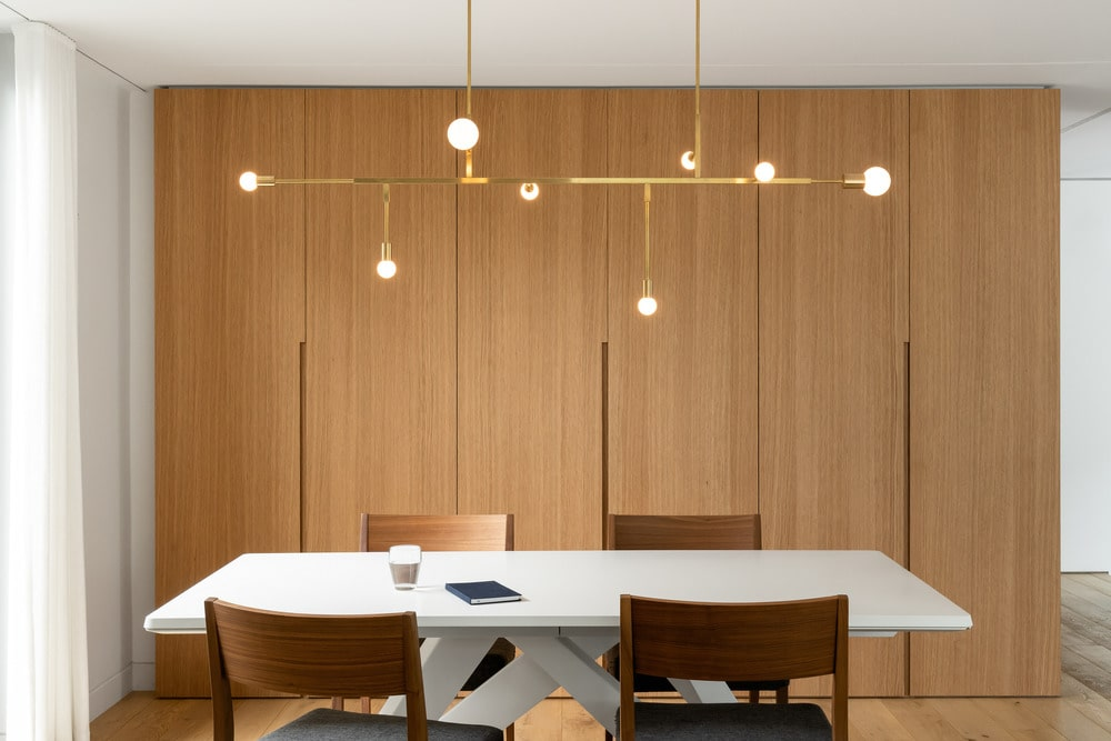 The white dining chair is surrounded by the wooden dining chairs topped with a modern chandelier.