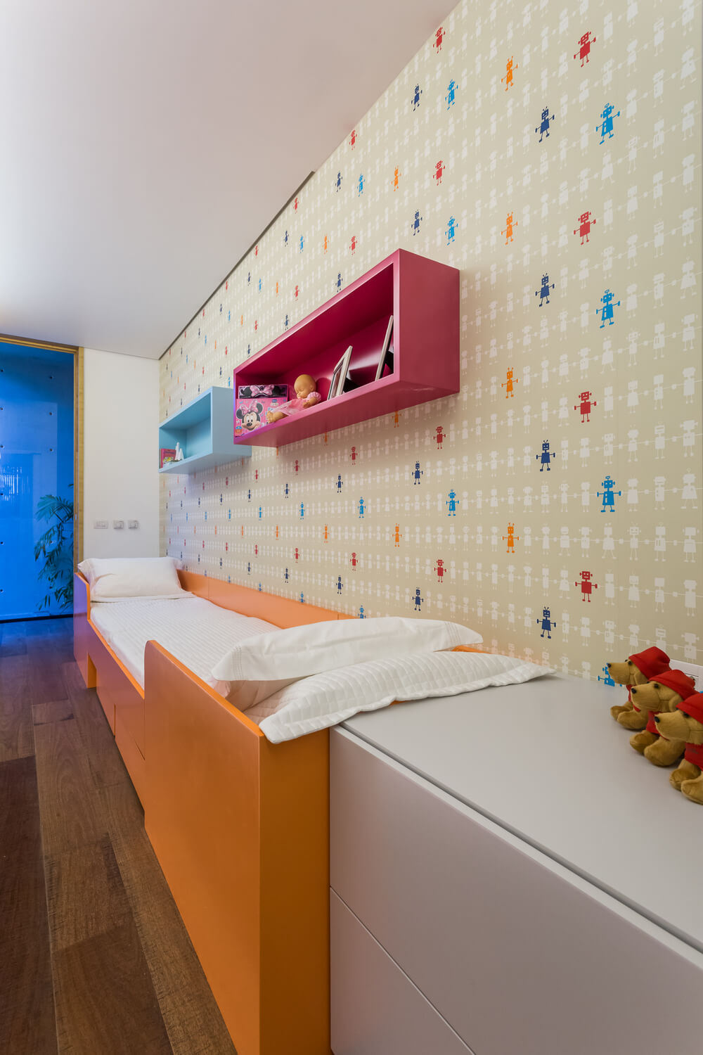 This is a child's bedroom that has a large orange bed, colorful hanging shelves above and a colorful patterned wallpaper.
