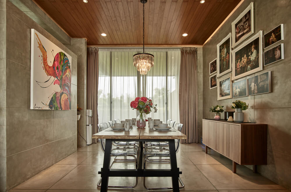 On the other side of the table is a waist-high dining room cabinet topped with a collection of framed artworks.