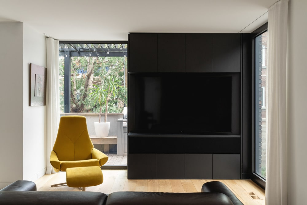The living room has a large black TV frame across from the black leather sofa that stands out against the light hardwood flooring.