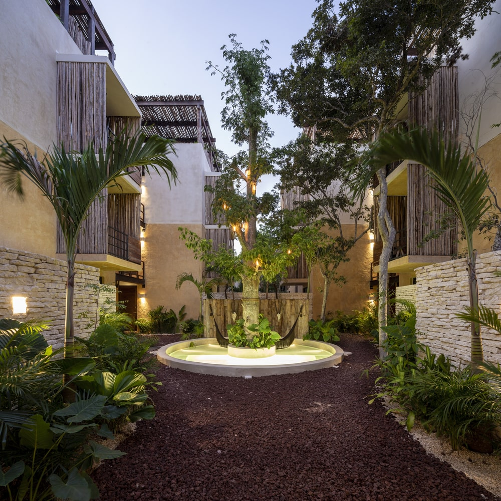 The dark tone of the pebbled walkway pairs well with the flanking tropical plants and trees lit by outdoor lighting.