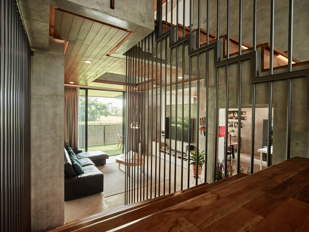 This is a view of the living room area from the vantage of the staircase lined with railings on the side.