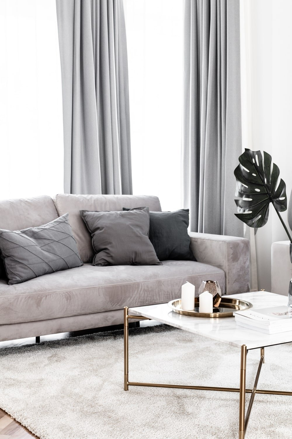 The golden metallic tone of the coffee table's frame makes it stand out against the light area rug.