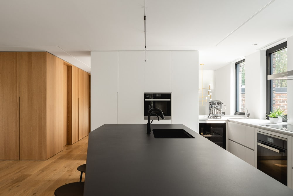 This is a close look at the kitchen island with a black countertop that stands out against the bright walls and ceiling.