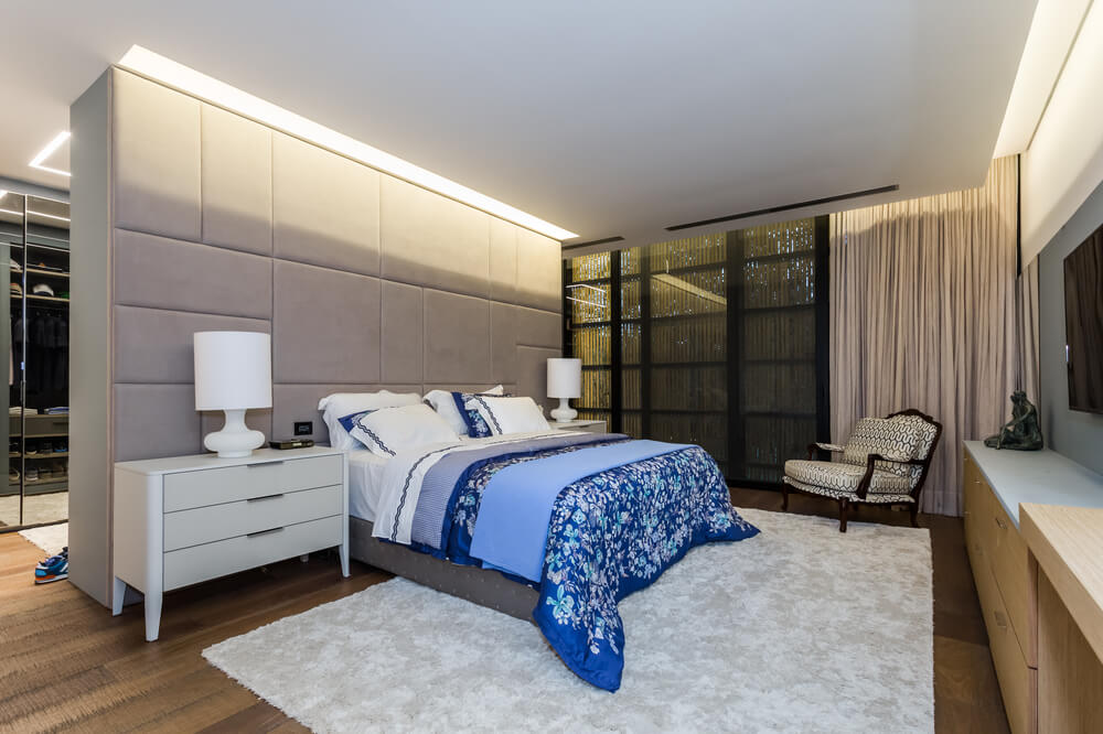 This bedroom has a bed flanked with bedside white drawers bearing table lamps.