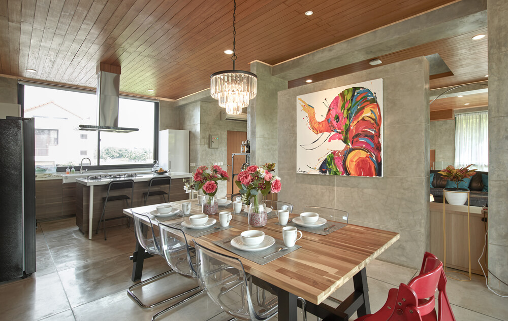 This is a close look at the dining area with its wood-top rectangular dining table adorned with a colorful wall-mounted artwork on the side.