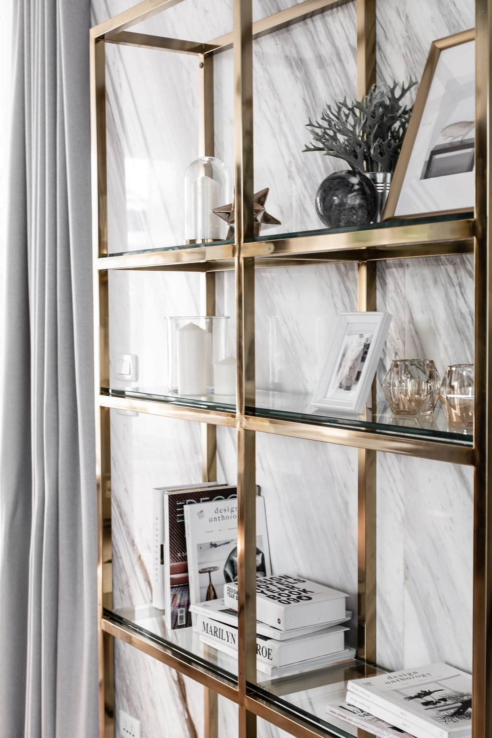 Across from the set of sofas is this wall-mounted metallic shelving system.