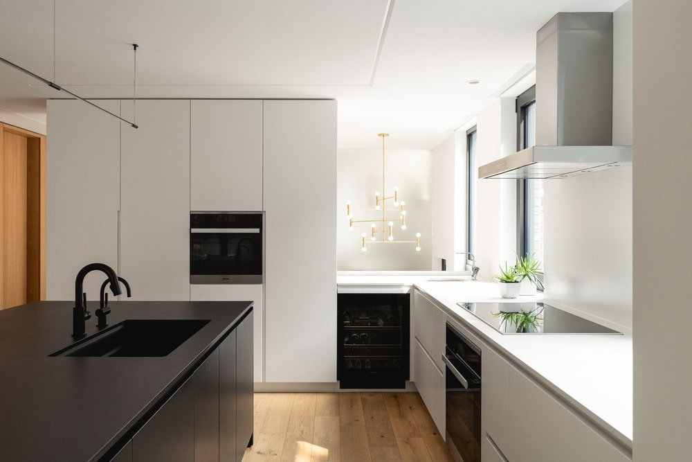 The black appliances stand out against the white cabinetry lining the walls.