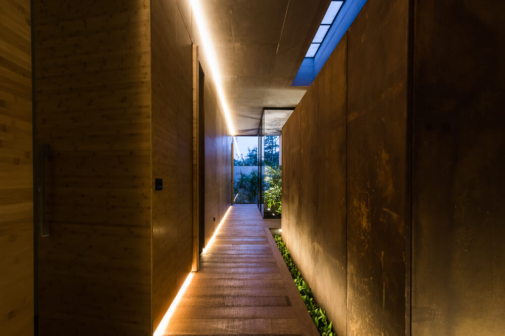 This is a hallway with wooden walls, wooden flooring, modern warm lighting and a skylight.