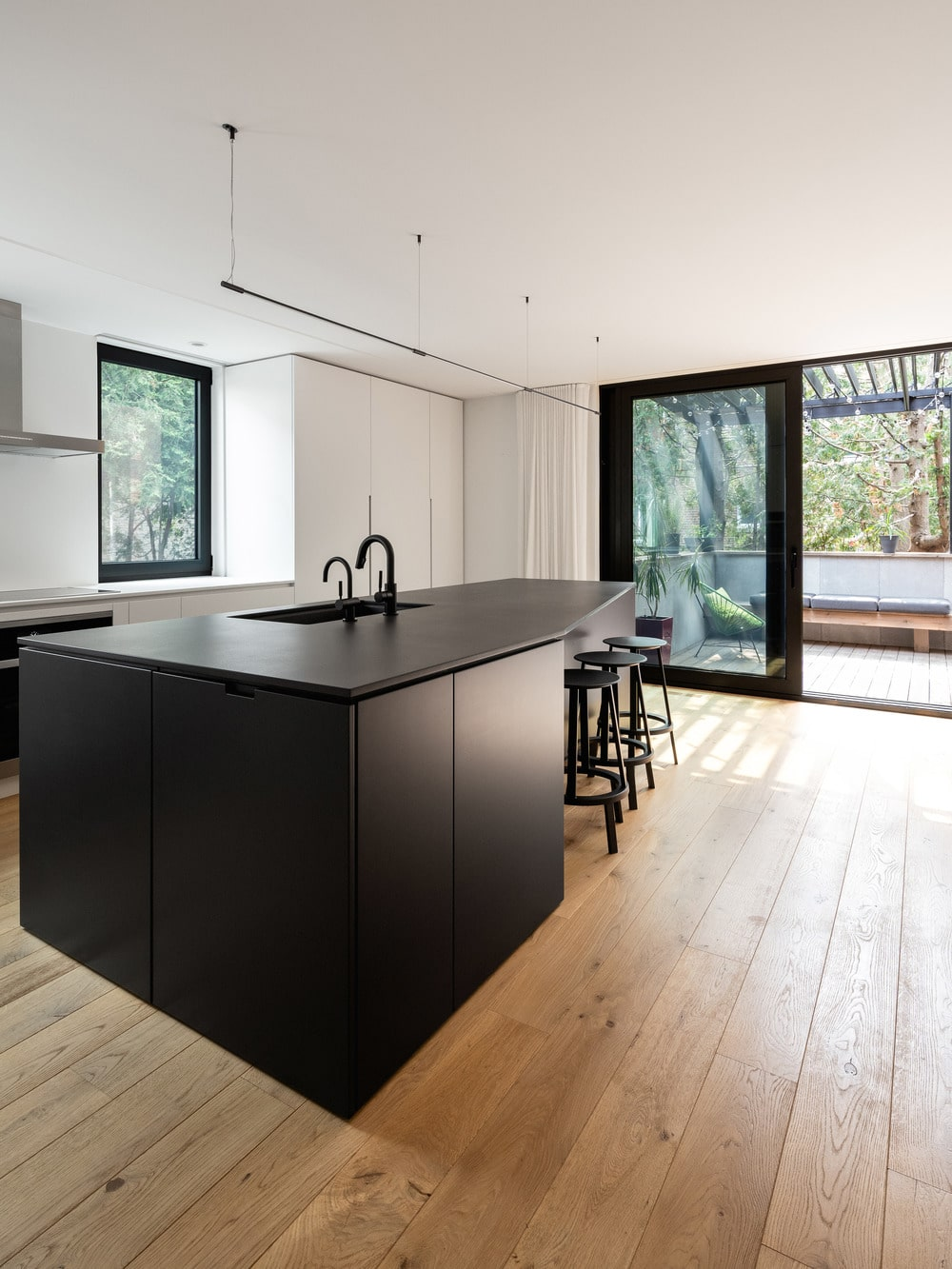The kitchen has a large black kitchen island that stands out against the hardwood flooring.