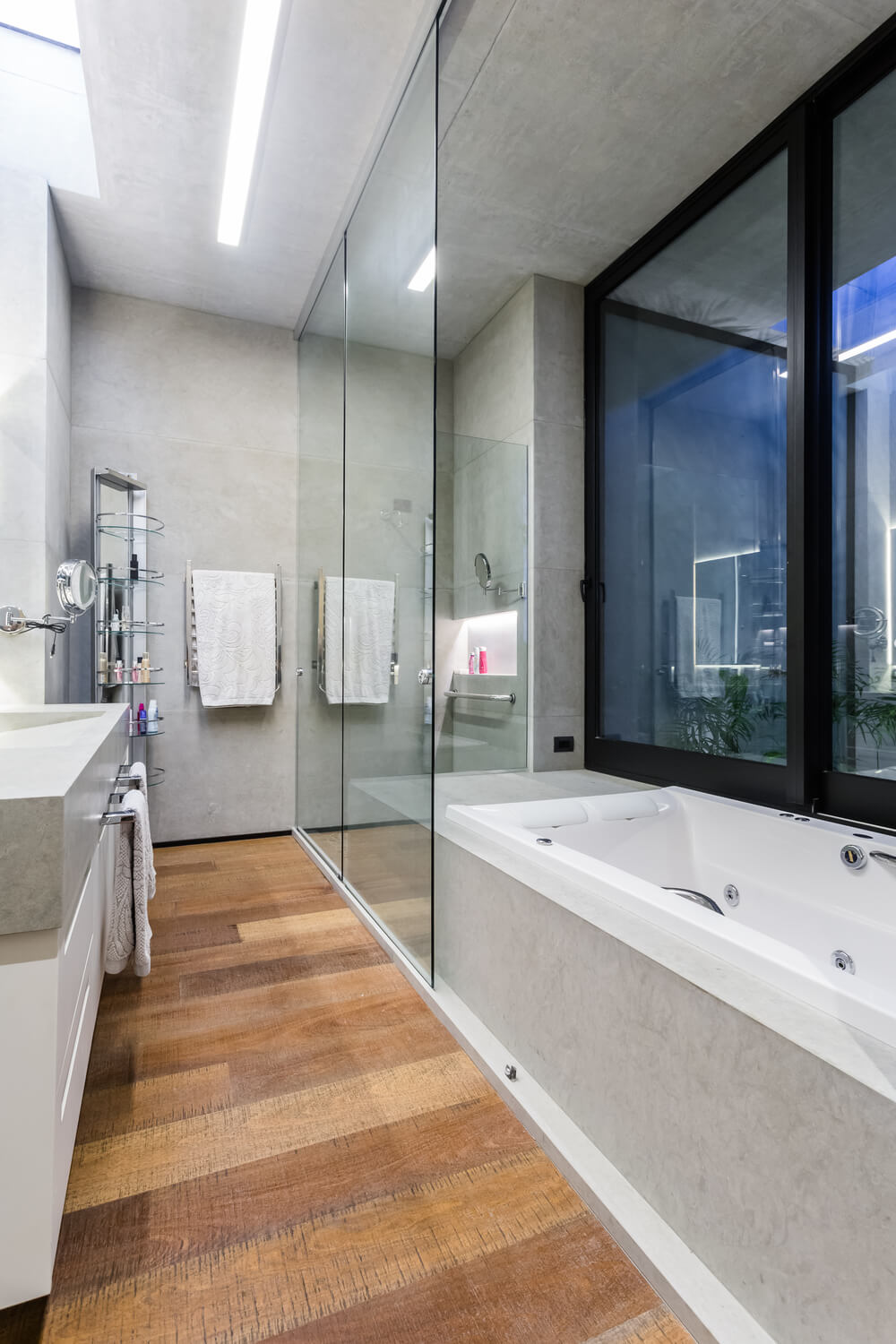 This bathroom has a glass-enclosed shower area on the far corner next to the bathtub by the window.