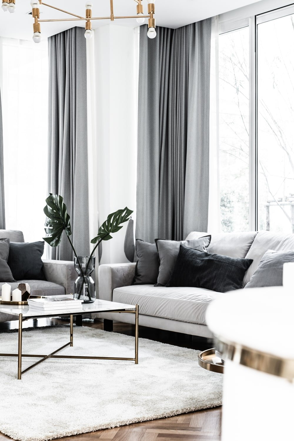 The family room is brightened by the surrounding tall windows paired with gray curtains.