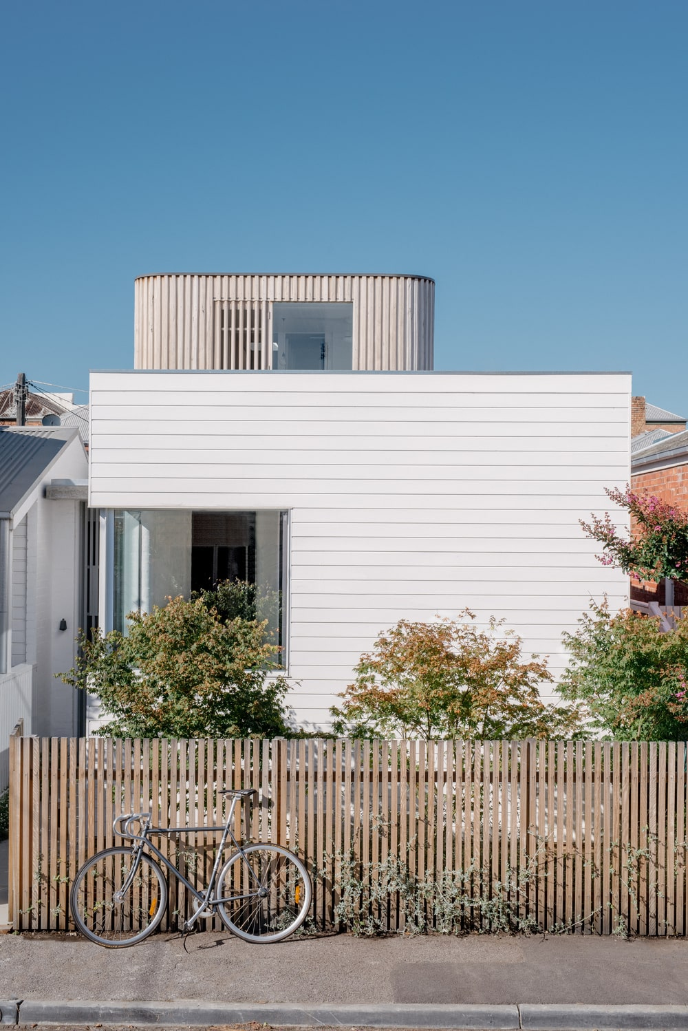 This is a view of the house exterior with bright white exterior walls and a wooden fence surrounding the landscaping.