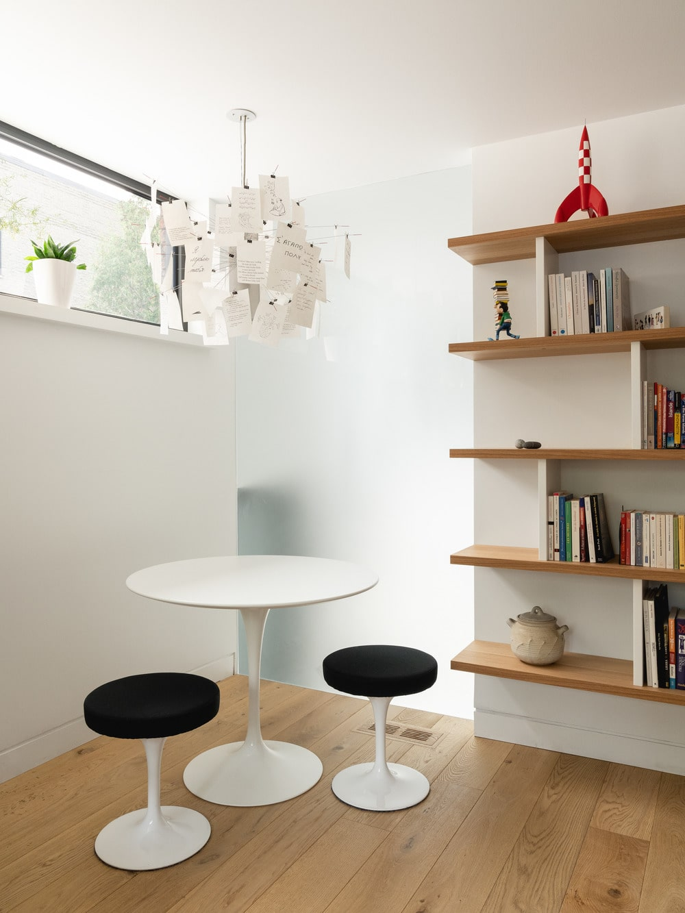 This is a corner library with a round white modern table next to a built-in modern shelf.