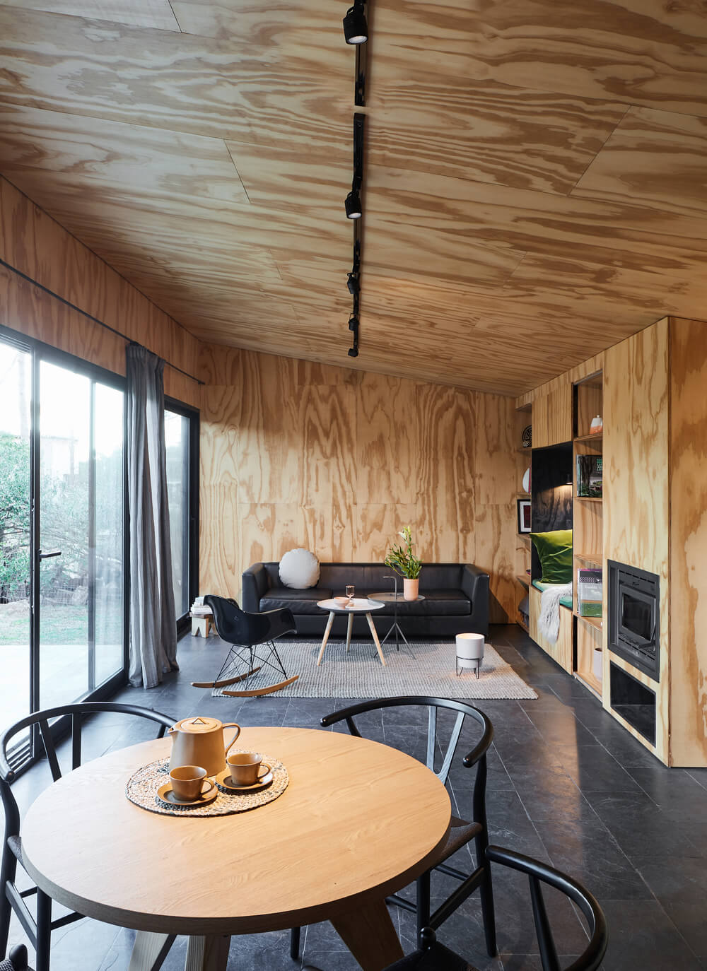 The great room has a consistent wooden tone on its walls and arched ceiling as well as the built-in wooden structure of the living room area.