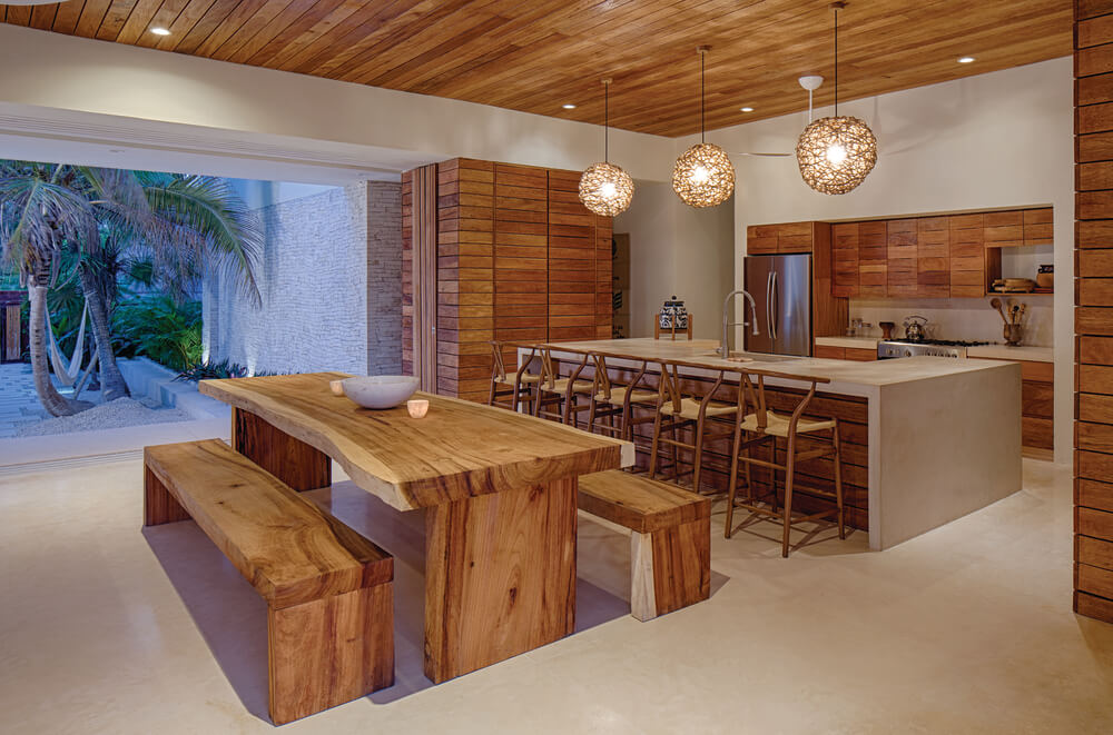 A few steps from the living room sofa is the wooden dining table and the large kitchen island topped with spherical pendant lights.