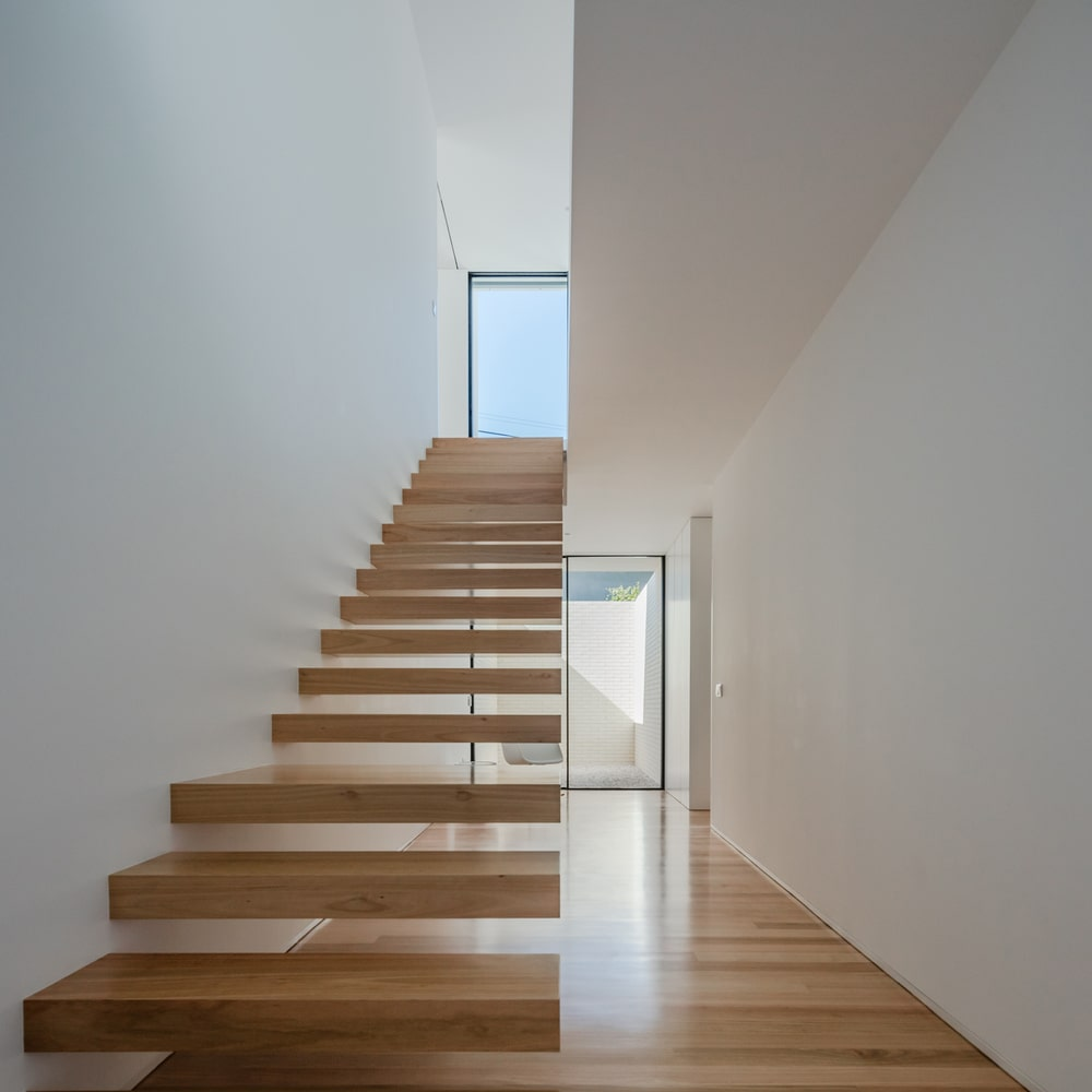 The wooden steps of the staircase match well with the hardwood flooring and contrast the bright walls.