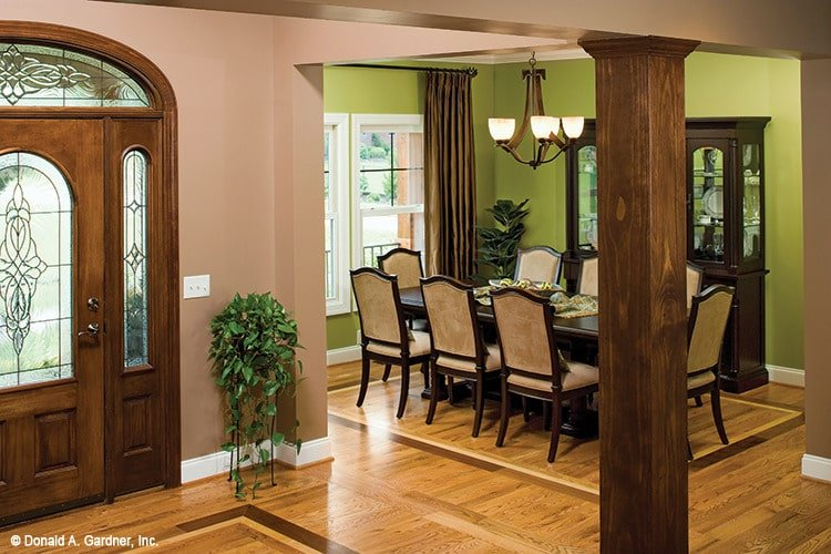 The dining room sits next to the foyer and offers a dark wood display cabinet and a rectangular dining set well-lit by a glass chandelier.