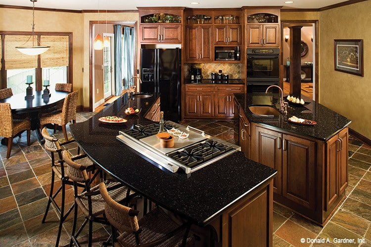 Eat-in kitchen with wooden cabinetry, black appliances, granite countertops, and two islands.