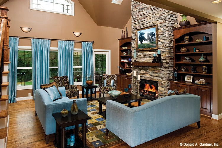Living room with a stone fireplace, wooden built-ins, patterned chairs, and blue sofas that match the draperies.