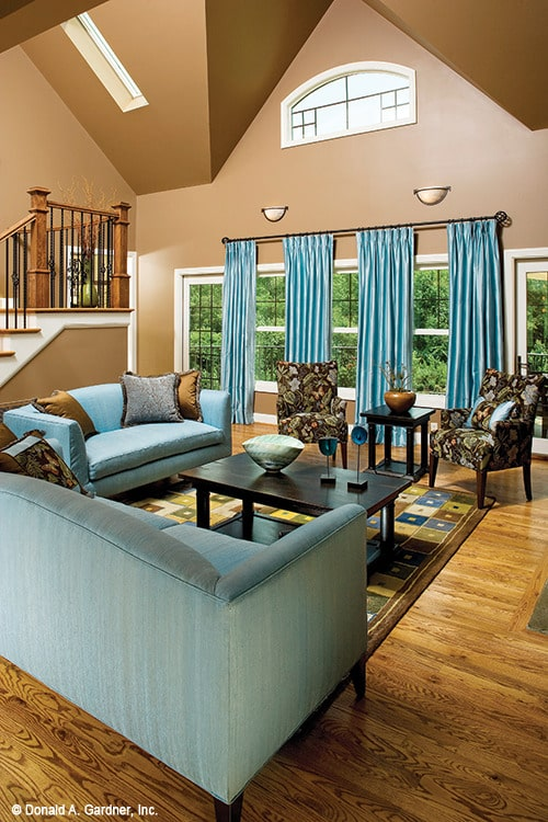 The living room includes a high vaulted ceiling fitted with a skylight and a curved transom window.