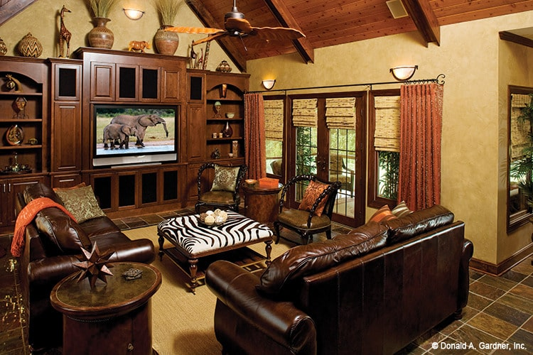 Family room with brown leather seats, a zebra ottoman, and a flatscreen TV.