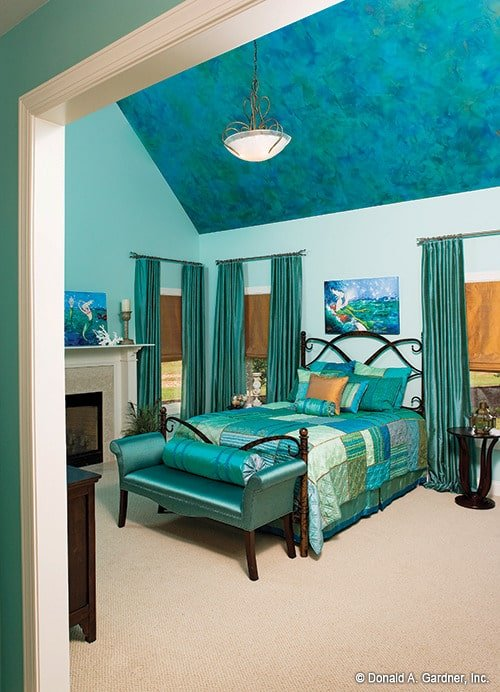 The primary bedroom features a cool blue palette. It includes a cathedral ceiling, a fireplace, and an ornate wooden bed complemented with an upholstered bench.