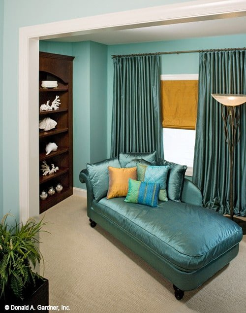 Sitting room with dark wood shelving, a classy chaise lounge, and matching draperies.