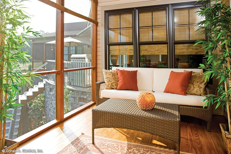 Back porch with screened windows and a wicker sofa set.