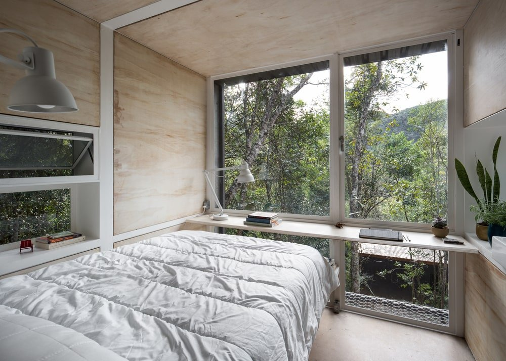 At the foot of the bed is the built-in desk of the study area brightened by the large glass wall.