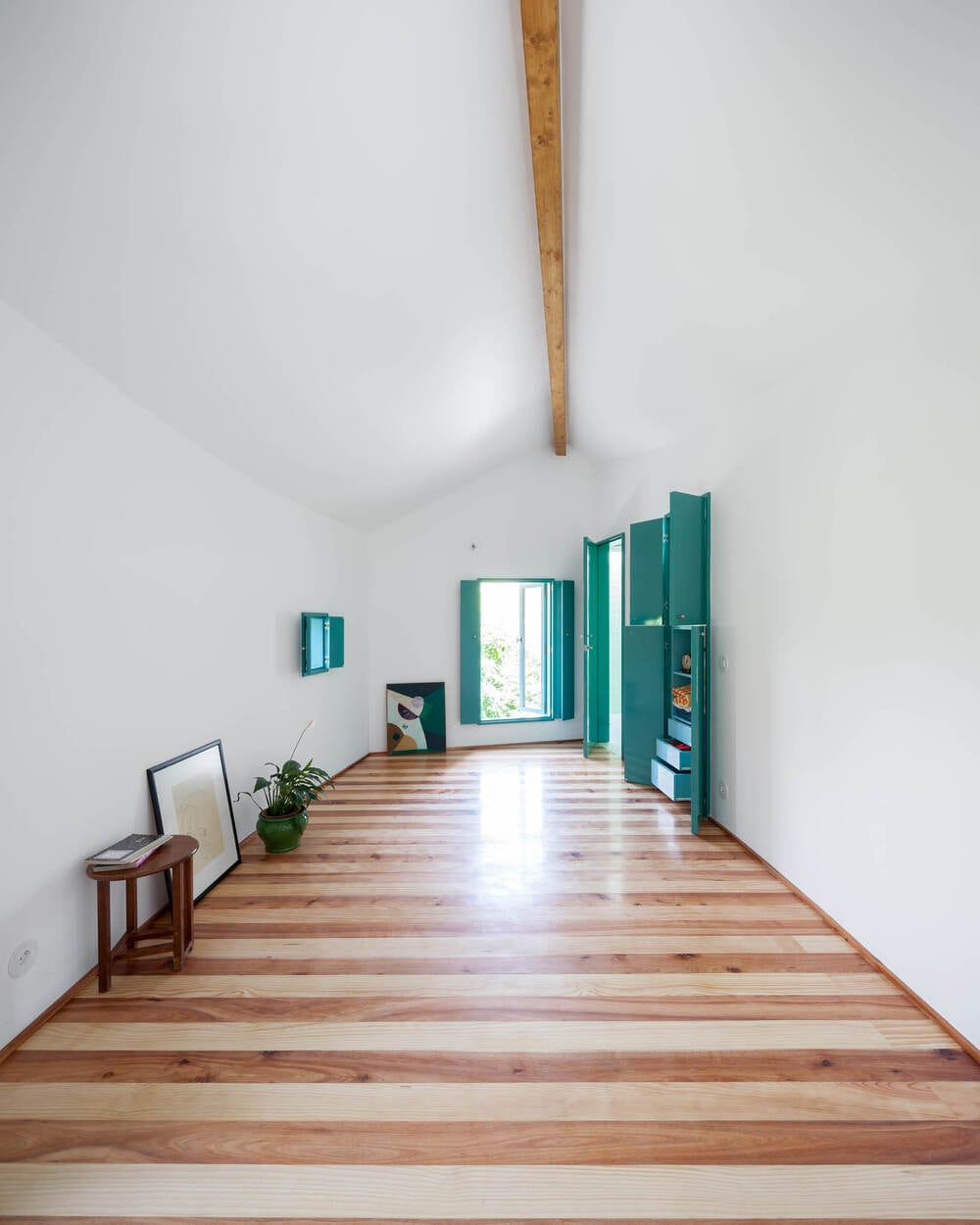 This is the large interior that has a patterned hardwood flooring paired with white walls and white cathedral ceiling with a single exposed beam in the middle.