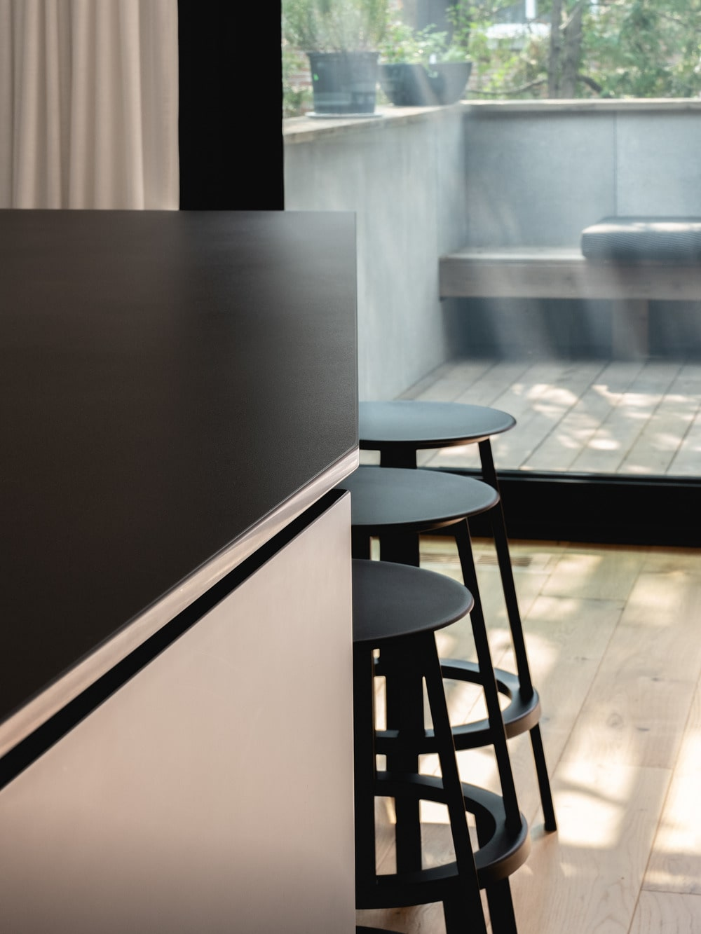 This is a close look at the kitchen island and its three black kitchen stools.