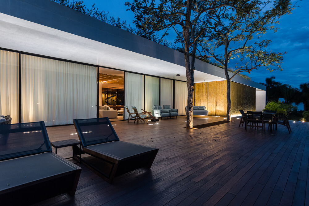 The part of the wooden deck poolside area is adorned with warm outdoor lighting.