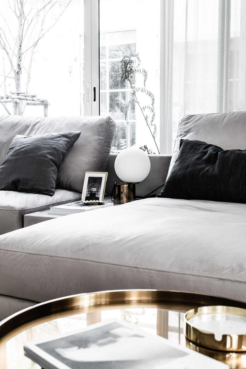 The gray tones of the sofa and its throw pillows give a nice contrast to the golden metallic round side table.