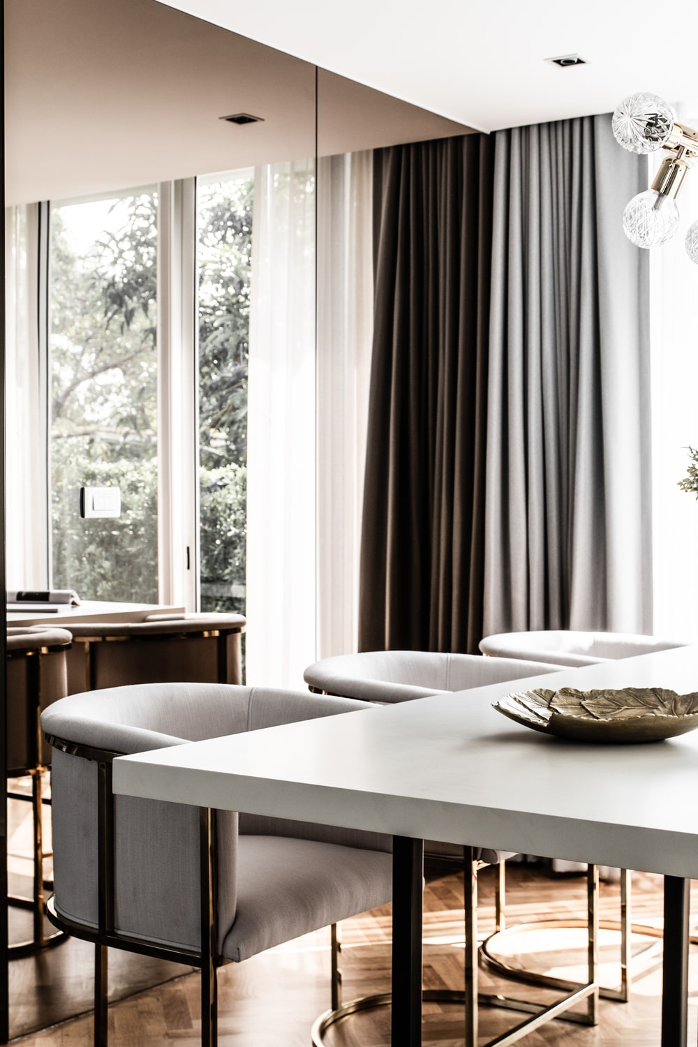 The large rectangular dining table is paired with gray cushioned arm chairs.