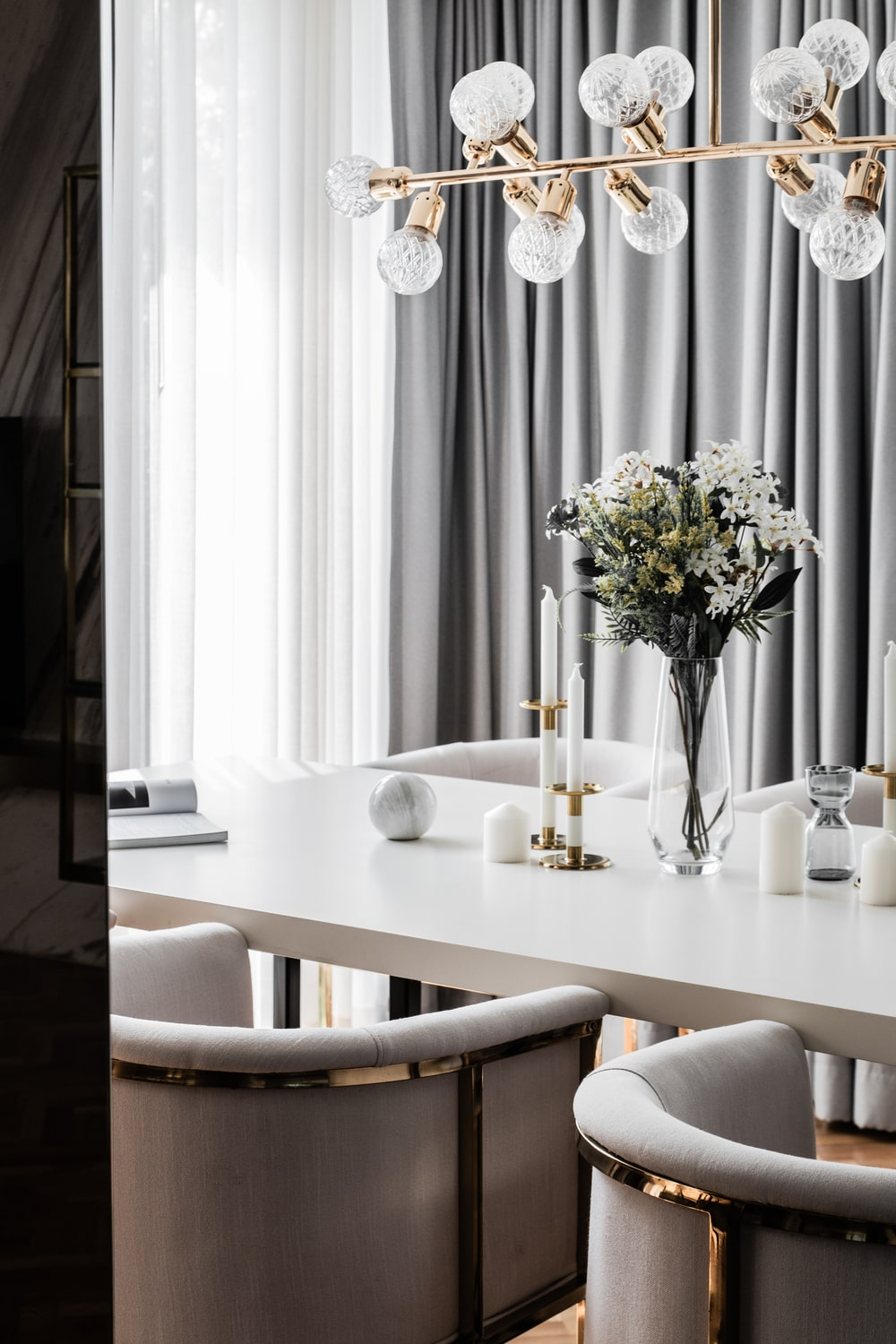 The white modern dining table of the dining area is topped with a set of modern decorative chandelier.