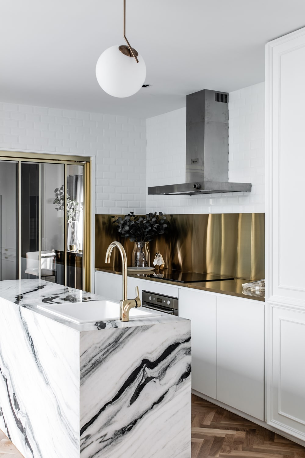 The backsplash of the kitchen counter matches with the faucet and the frame of the sliding door.