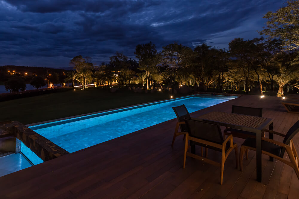 This view showcases the pool's ethereal lighting and the outdoor lighting of the trees in the distance.