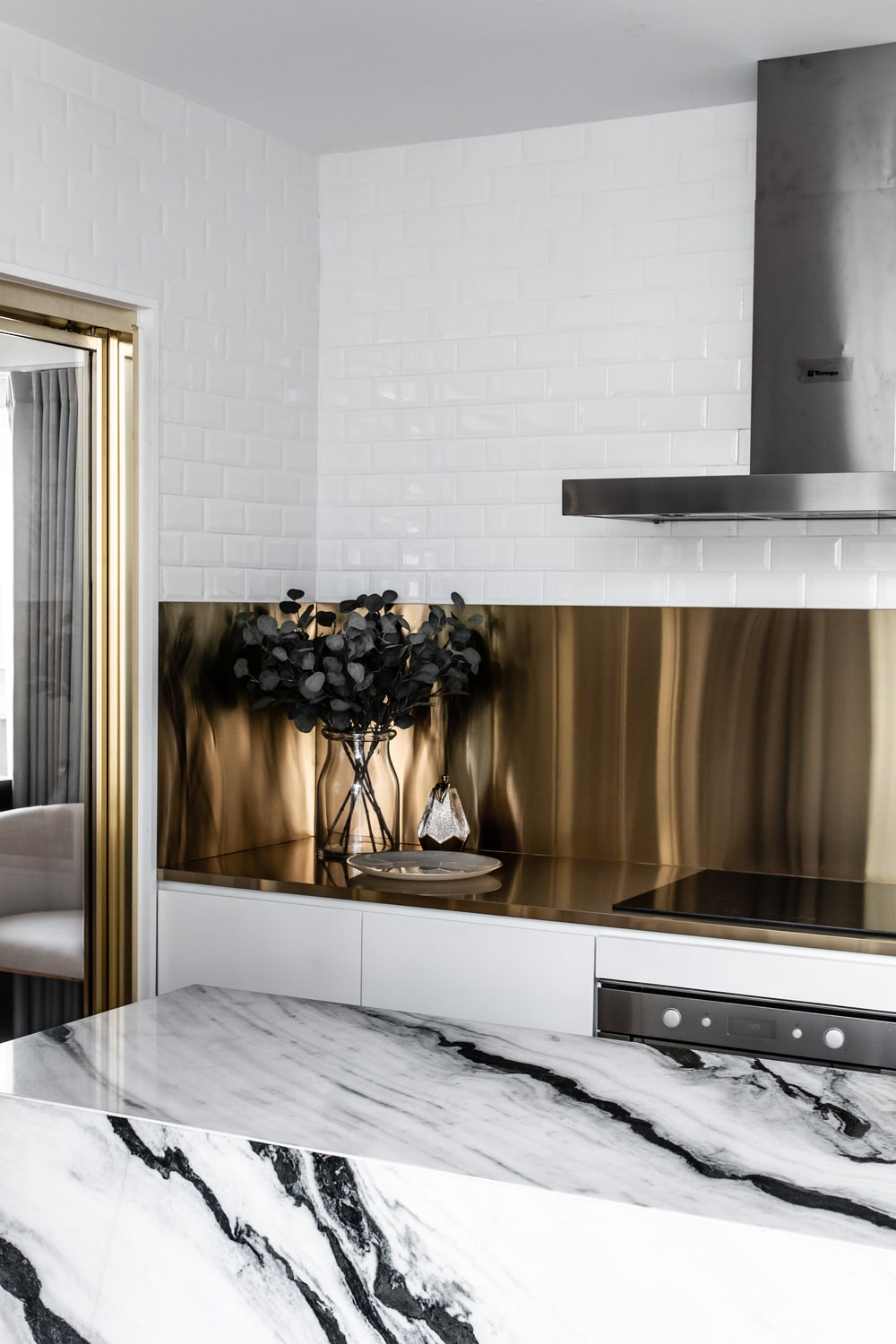 This is a closer look at the golden backsplash of the kitchen counter and its stainless steel vent hood.