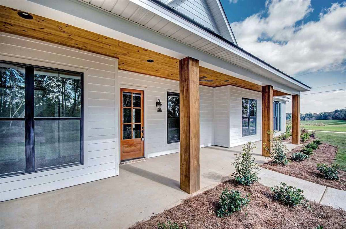 Front covered porch with wooden posts and a glazed entry door fixed against the white siding.