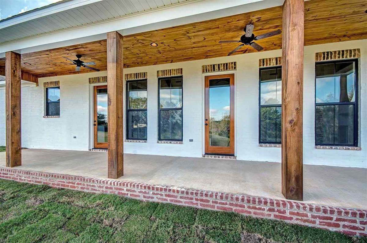 Rear covered porch with two glass doors, aluminum framed windows, and wooden columns.