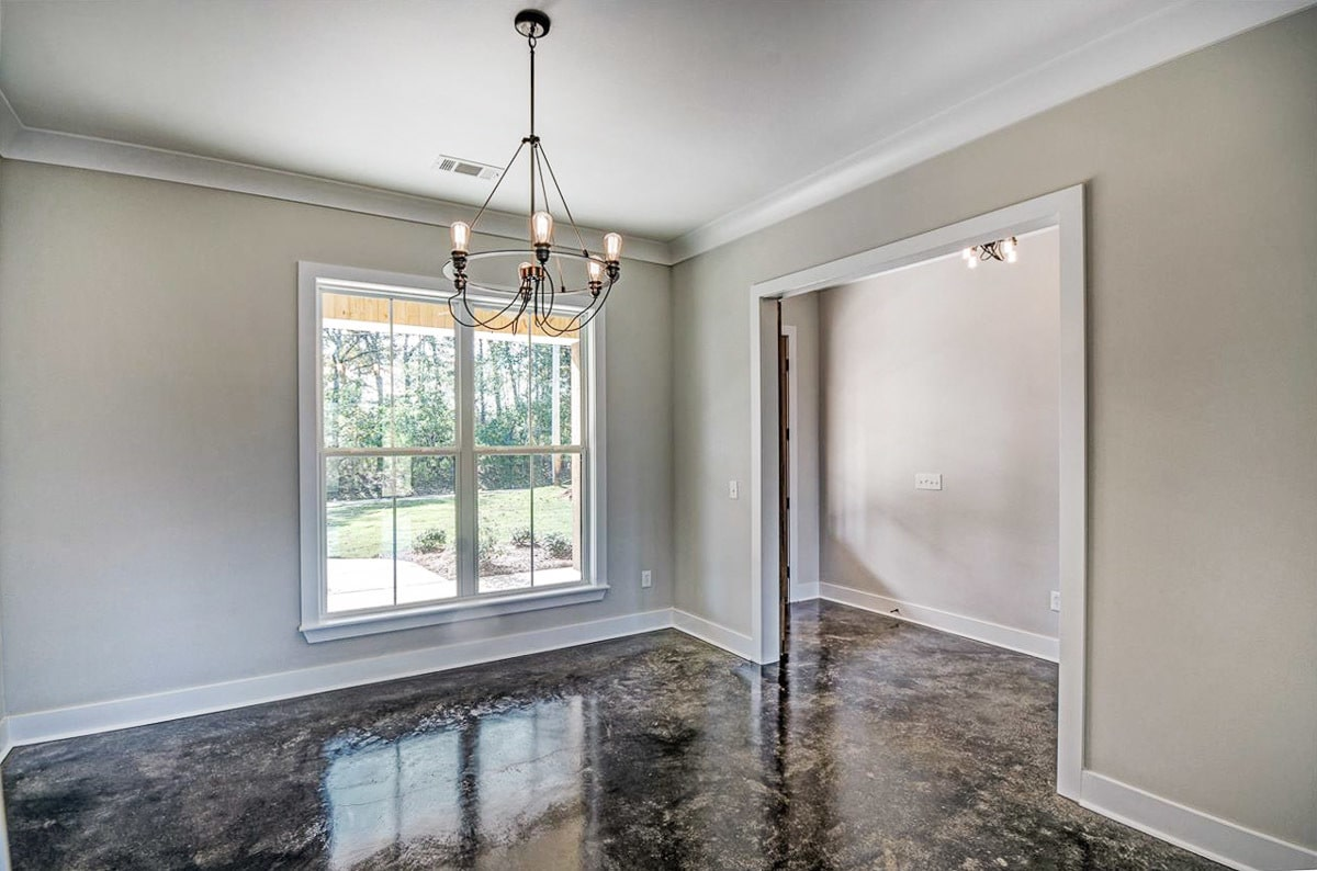 The formal dining space has gray walls, a white framed window, and a bulb chandelier.