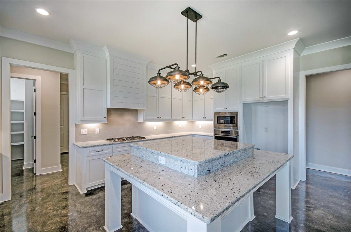 The kitchen is equipped with a double wall oven. built-in cooktop, white cabinetry, and a raised center island.
