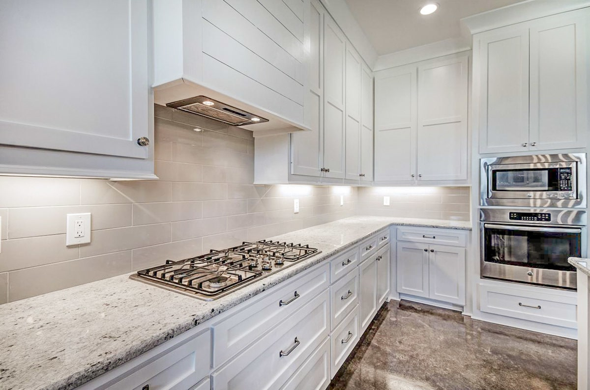 A closer look at the white cabinetry, double wall oven, and a built-in cooktop fitted on the granite countertop.