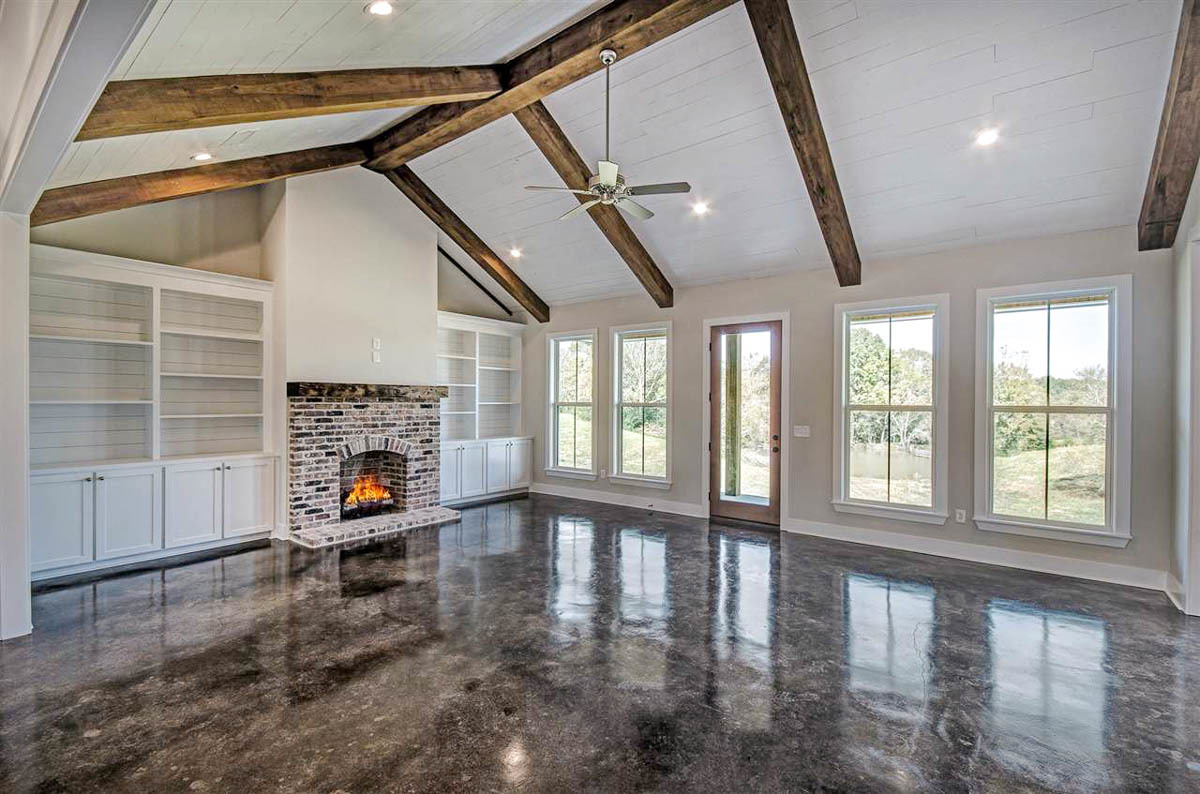 Living room with beamed ceiling, a brick fireplace, and white built-ins.